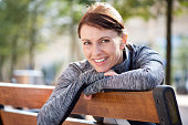 Portrait of a smiling sports woman relaxing outside on bench