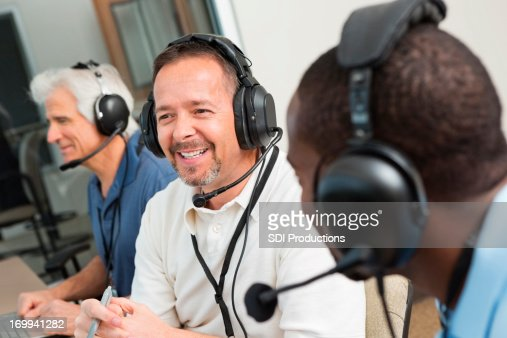 Smiling sportscasters discussing game in the media box