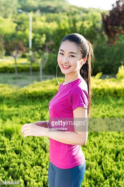 smiling sporty girl in headphones outdoors