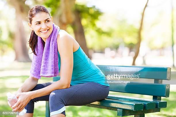 Souriante sportive femme de détente sur banc
