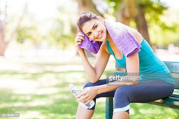 微笑む女性ワイピングスポーティな「Sweat (スウェット)」で、公園のベンチ