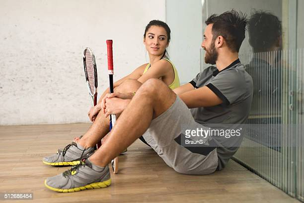 Smiling squash players resting on a court and talking.