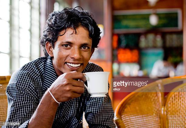 Lächelnd Sri-lankische junge Mann trinkt Tee in einem shop.