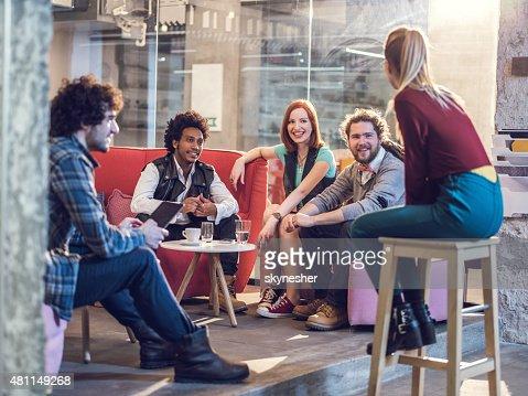 Smiling start up team communicating on a break.