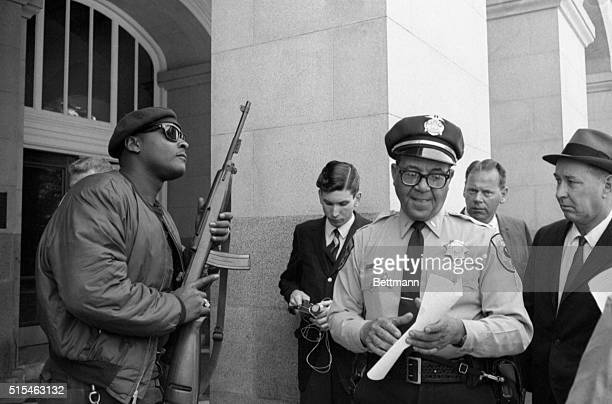 A smiling State Police Lt Ernest Holloway grabs the arm of a member of the Black Panther Party as he tries to push past him into the State Capitol...