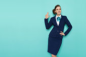 Happy stewardess in blue formal wear is showing pistol hand sign, smiling and looking at camera. Three quarter length studio shot on turquoise background.
