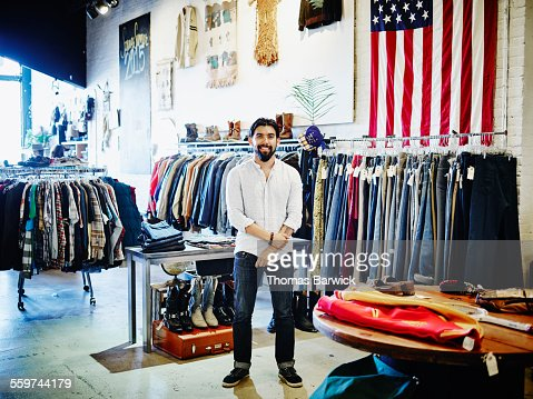 Smiling store owner in mens clothing store