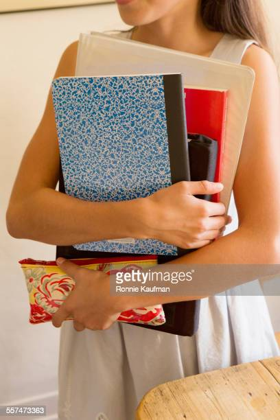 Smiling student carrying books and pencil case