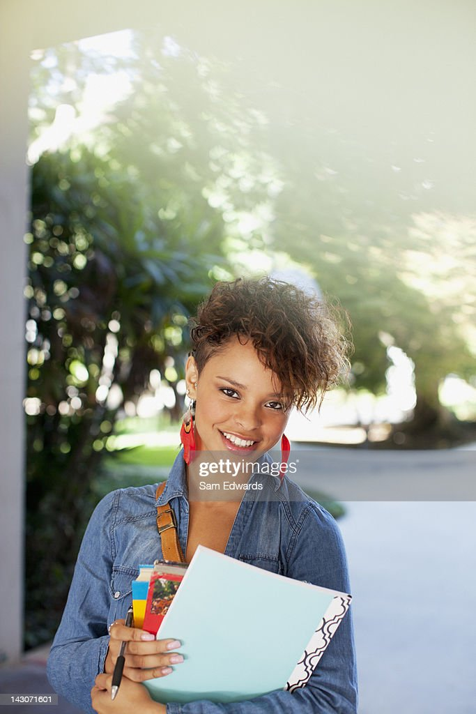 Smiling student carrying folder : Stock Photo