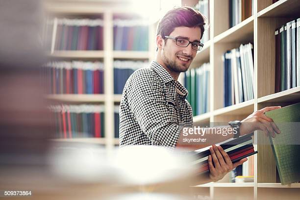 Smiling student choosing books in library and looking at camera.