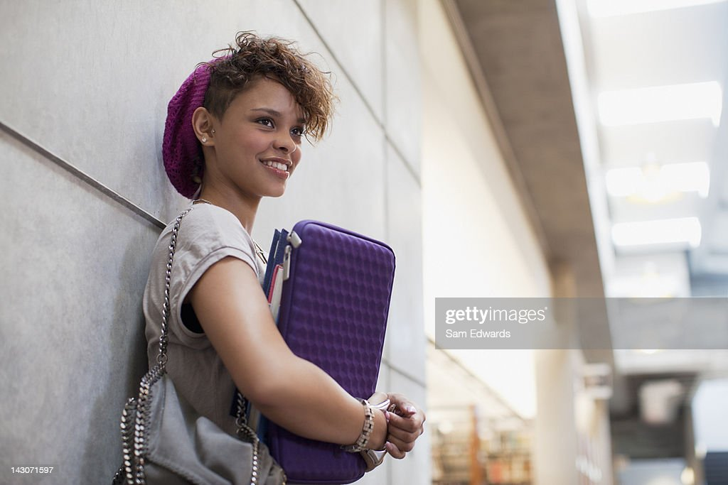 Smiling student leaning against wall : Stock Photo