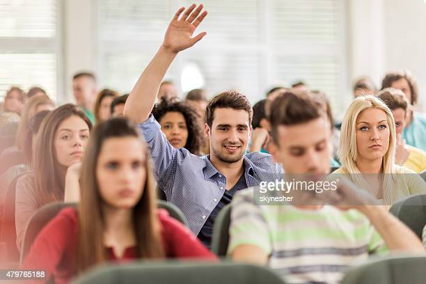 Smiling student raising hand to answer question at lecture hall.