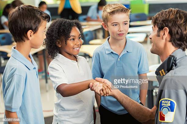 Smiling student shakes hands with police officer