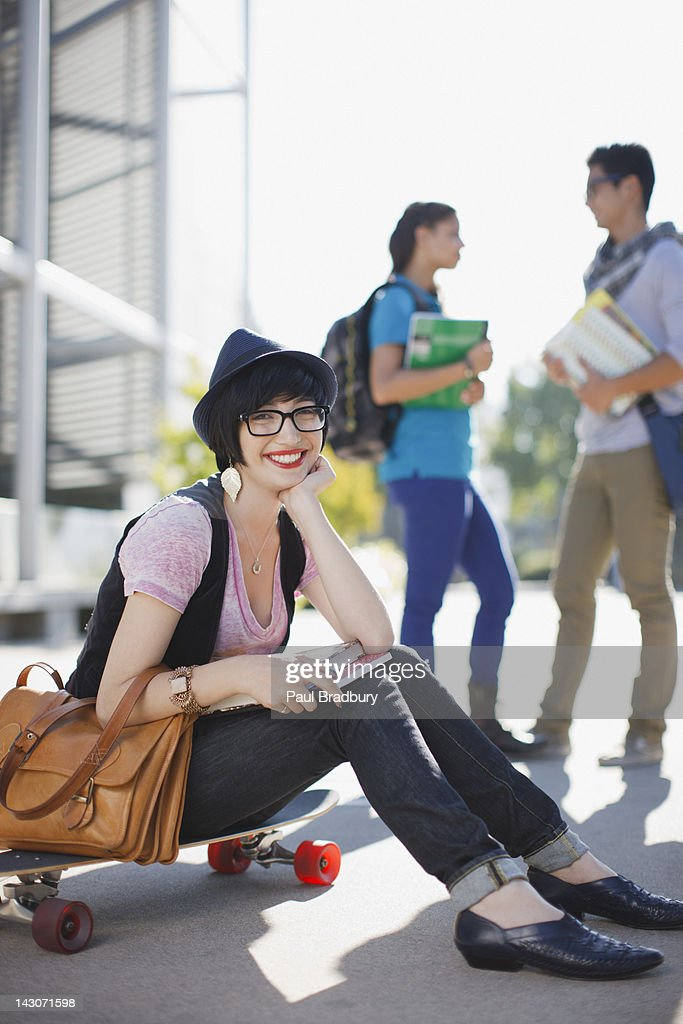 Smiling student sitting on skateboard : Stock Photo