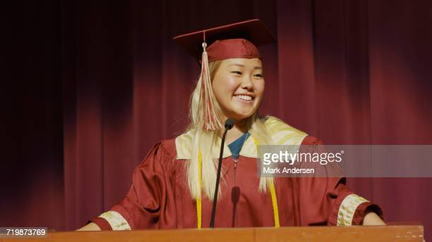 Smiling student speaking at podium on stage during graduation ceremony