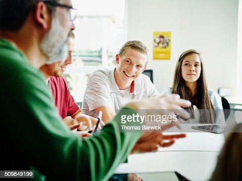 Smiling students listening to teacher lecture