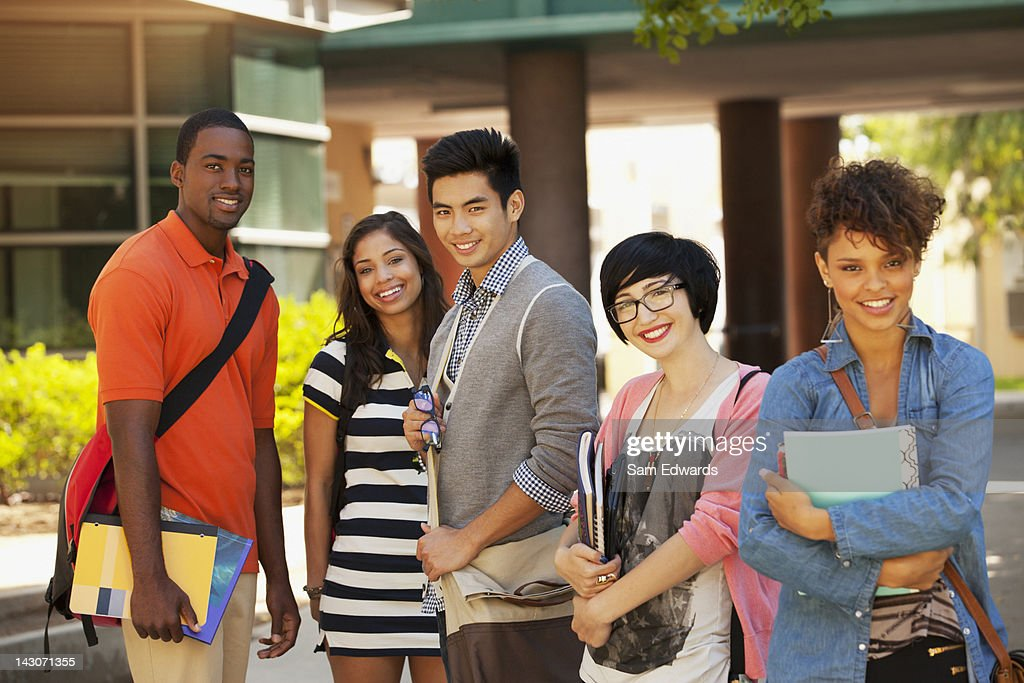 Smiling students standing together outdoors : Stock Photo