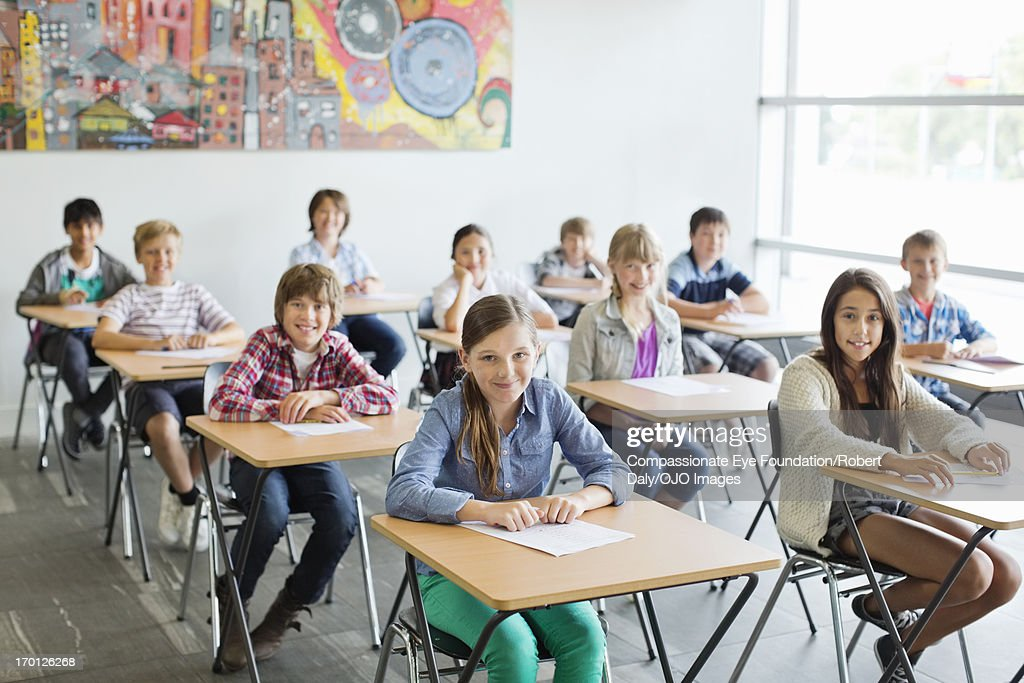 Smiling students taking a test in classroom