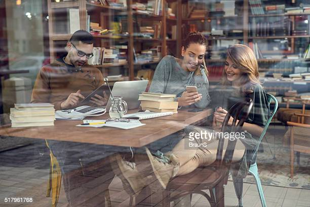Sonriente de estudiantes utilizando la tecnología inalámbrica en la biblioteca.