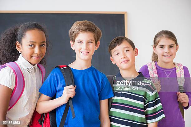 Smiling students wearing backpacks in front of chalkboard