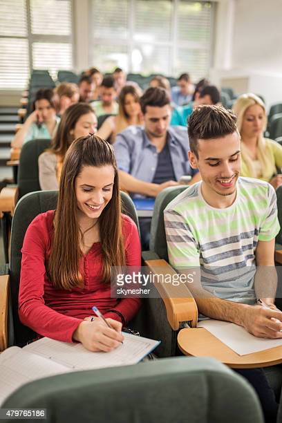 Smiling students writing in lecture hall.