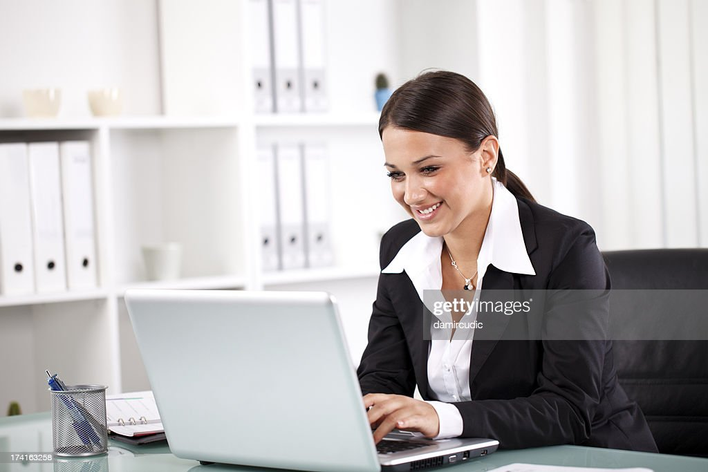 Smiling successful businesswoman working on laptop : Stock Photo