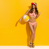 Beautiful smiling woman with brown long curly hair, posing in sunlight in pink bikini, cork heels and red sun visor and holding beach ball under the arm. Full length studio shot on yellow background