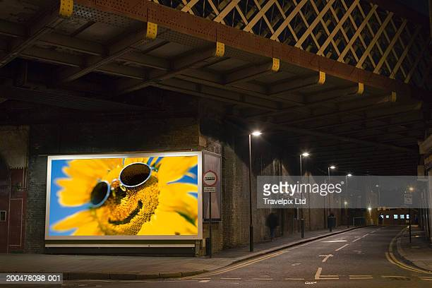 Smiling sunflower on billboard beside dark road