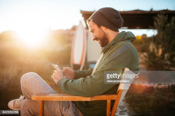 Smiling surfer using smartphone