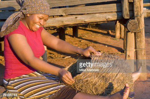 A smiling Swazi woman working on making a basket while sitting in the sun. Swaziland