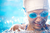 Female swimmer wearing swimming cap and goggles smiling in the water