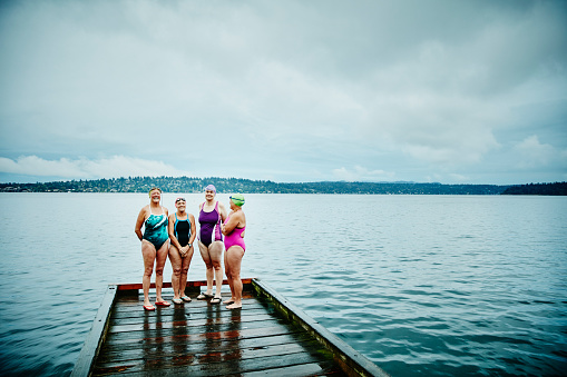Smiling swimmers preparing for morning swim