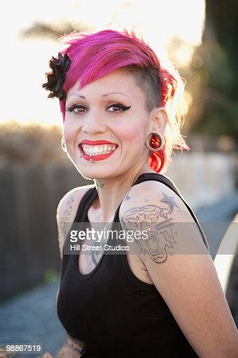 Smiling, tattooed Hispanic woman