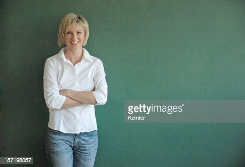 smiling teacher at blackboard