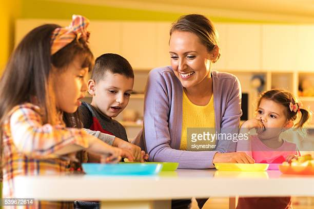 Smiling teacher enjoying with kids during lunch break at preschool.