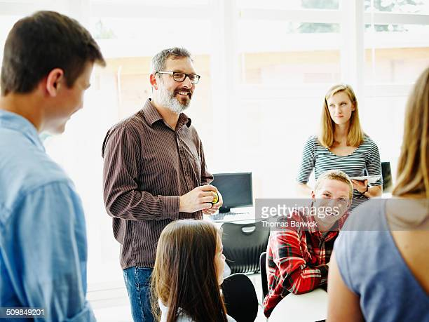 Smiling teacher in discussion with students