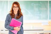 Smiling female teacher standing in classroom in front of blackboard