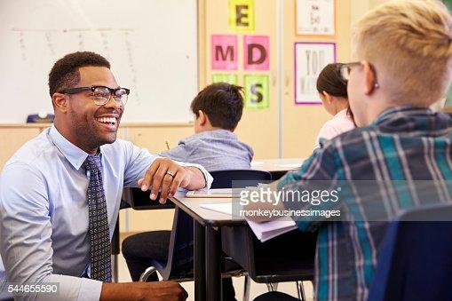 Smiling teacher kneeling beside elementary school pupil's desk : Stock Photo