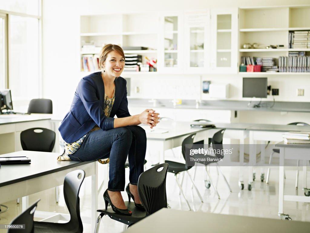 Smiling teacher sitting on desk in classroom : Stock Photo
