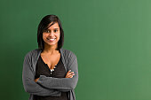 Smiling teacher with arms folded in front of blackboard