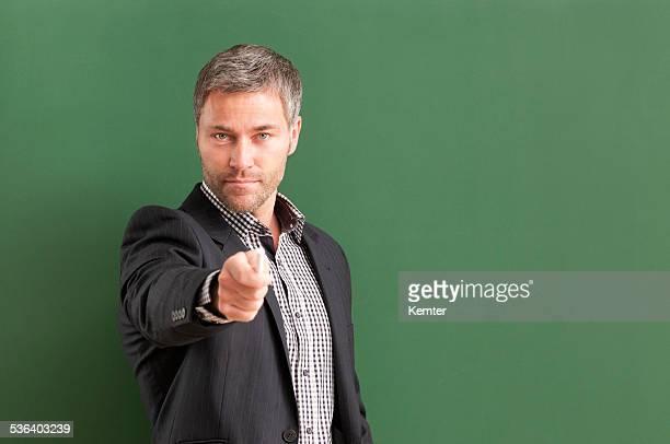 笑顔の先生、グレーのヘアカメラを指す
