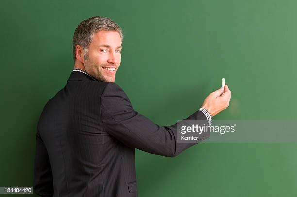 smiling teacher writing at blackboard