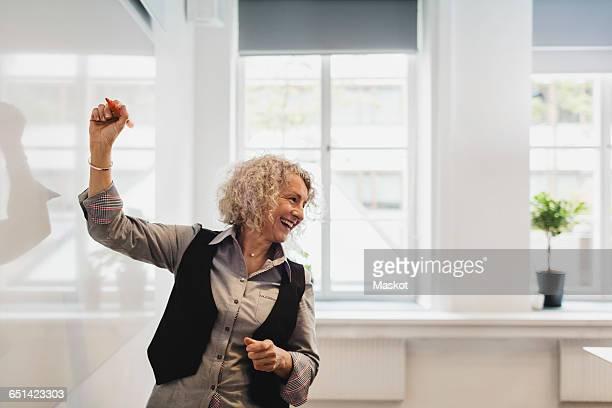 Smiling teacher writing on whiteboard in language class