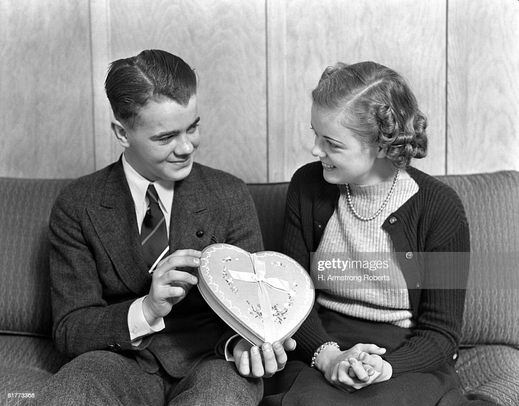 Smiling Teen Couple Sitting On A Sofa The Boy Dresed In Suit & Tie Is Giving The Girl Wearing Pearls And A Cardigan A Heart Shaped Box Of Chocolate. : Stock Photo