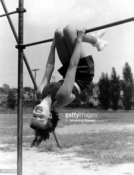 Smiling teen girl on playground hanging upside down on monkey bars.