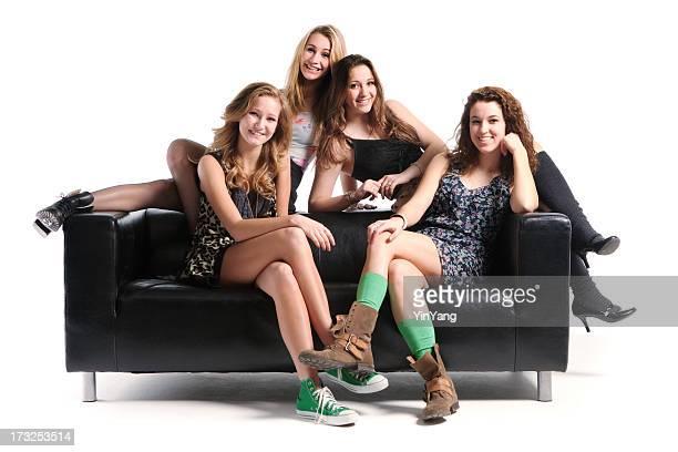 Modèles souriant adolescents avec canapé noir sur fond blanc Hz