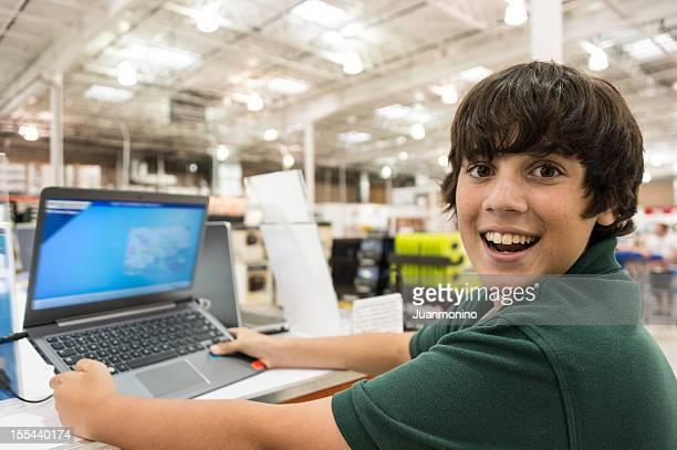 Souriant jeune garçon choisir un ordinateur portable