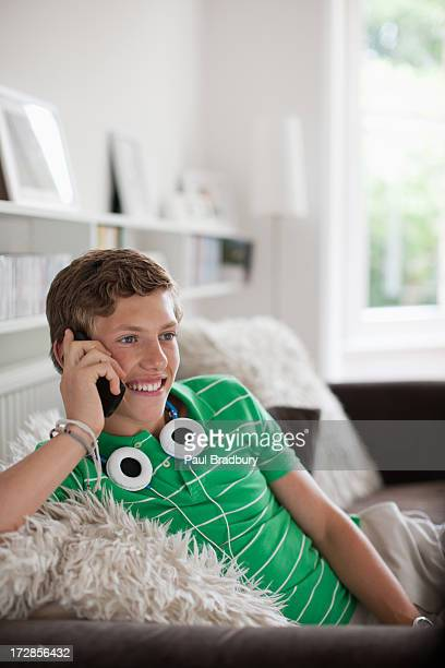 Smiling teenage boy in living room talking on cell phone