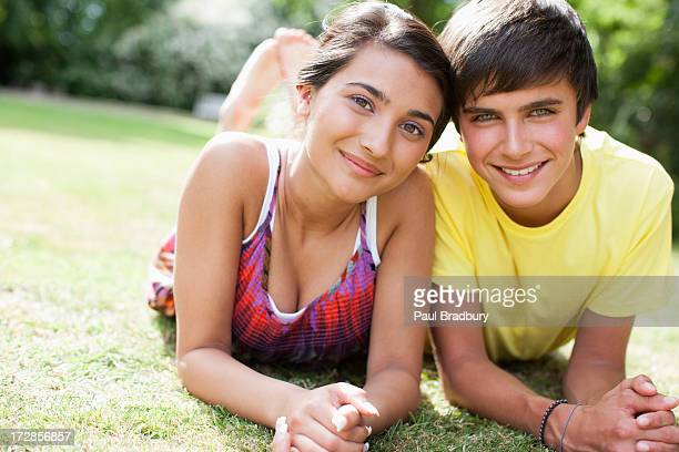Smiling teenage couple laying in grass together