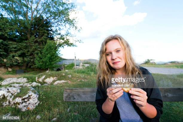 Smiling teenage girl eats truffle olive oil bruschetta bread at a picnic table outdoors in Abruzzo, Italy, Europe